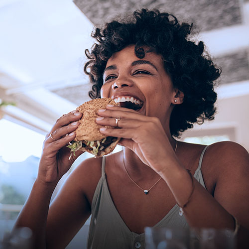 A woman eating a hamburger in a restaurant