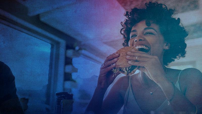 A woman eating a hamburger in a restaurant