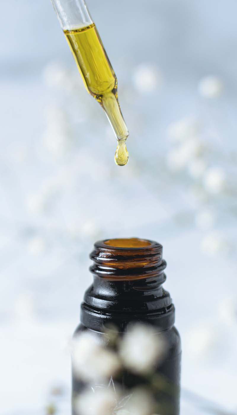 Hand with dropper removing CBD oil from bottle
