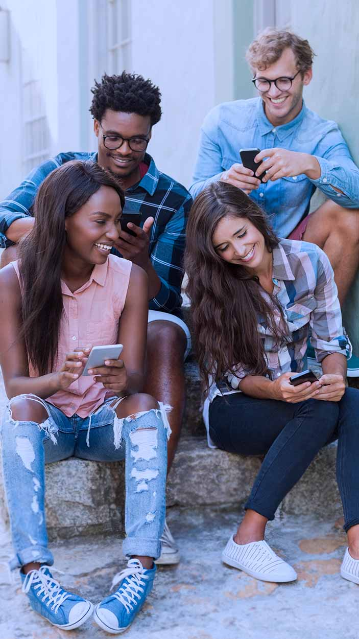 A group of people watching the sunset while one person takes photos with their phone.