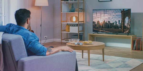 Man viewing programmatic linear tv ads on a television