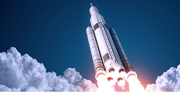 A rocket lifts off from Earth on starry night