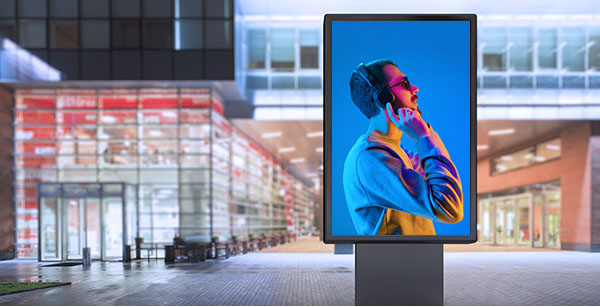 A bus shelter has a digital billboard showing a men's fashion advertisement