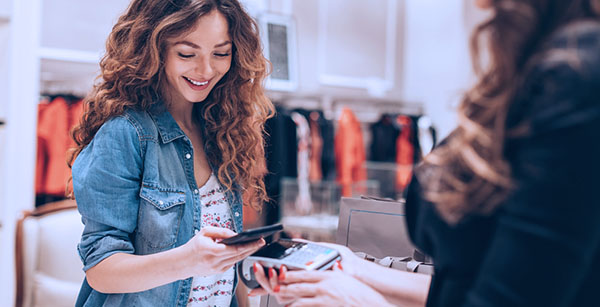 Young woman looking at phone while out shopping with purchases in hand