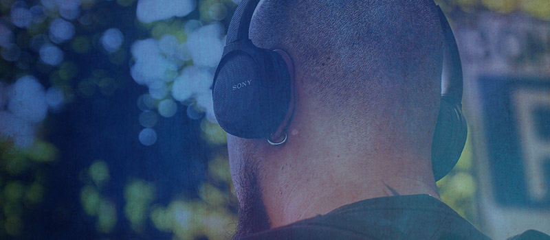 Man wearing headphones listening to digital audio